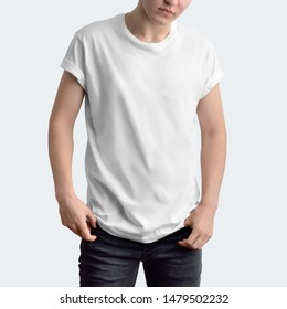 Attractive slim guy in a blank T-shirt and dark jeans on a white studio background. Frontal pose. 