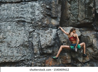 attractive slim muscular young woman rockclimber climbing on tough sport route on granite cliff, resting and chalking hands. outdoors rock climbing, exercising and active lifestyle concept.