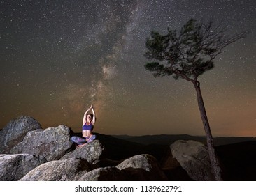 Attractive slim tourist girl sitting alone on top of huge boulder in lotus posture doing yoga under dark starry summer sky with Milky way. Tourism, recreation and active lifestyle concept. Siddhasana