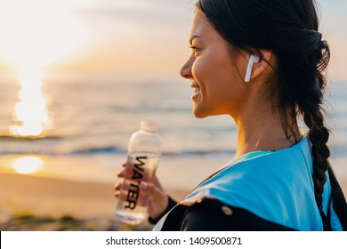 attractive slim woman doing sport exercises on morning sunrise beach in sports wear, thirsty drinking water in bottle, healthy lifestyle, listening to music on wireless earphones, smiling happy