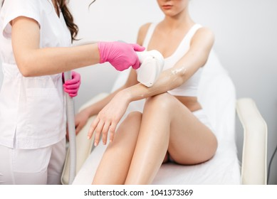 Attractive slim woman is receiving the laser epilation of her hands in beauty salon. The beautician is using special equipment.