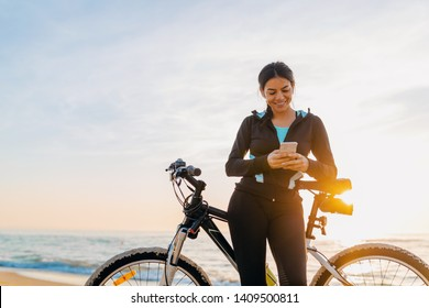 attractive slim woman riding bicycle, sport on morning sunrise beach in fitness suit, healthy lifestyle, listening to music on wireless earphones holding smartphone, relaxing smiling happy