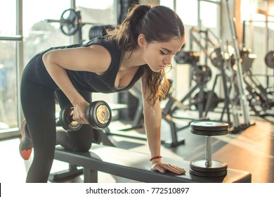 Attractive slim young sporty woman working out with weight in the gym.