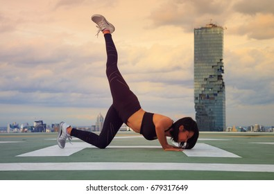 Attractive Slim young woman fitness ,work out on the roof of Helipad skyscraper,twilight sky scene in the cityscape background ,evening scene with city background ,weight loss concept