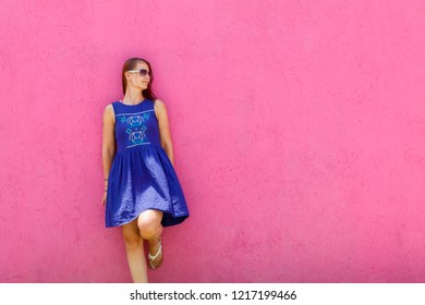 Attractive Slovak young woman posing by the pink wall