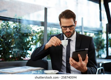 Attractive and smart business man using his tablet while having breakfast at coffee shop, businessman holding cup of coffee while read news on tablet