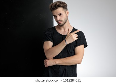 attractive smart casual man holding hands and pointing finger, standing on black and white background in studio