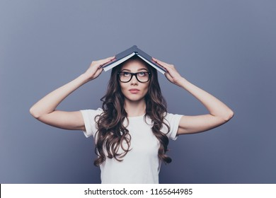 Attractive smart, clever, lovely stylish nice cute curly-haired brunette girl in casual white t-shirt and glasses, holding opened book on head like house, isolated on grey background