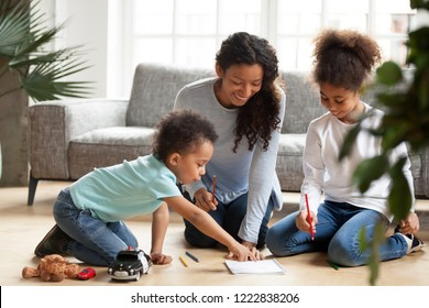Attractive smiling African American mother drawing with children sitting on warm floor in living room, toddler boy pointing to coloring book, little preschooler daughter with colorful pencil in hand