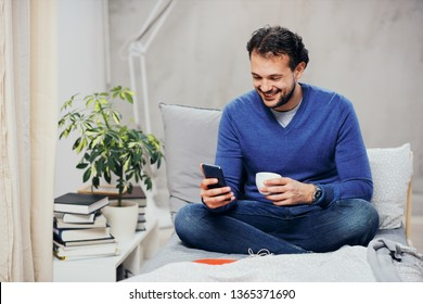 Attractive smiling arab man dressed casual sitting on bed in bedroom, drinking coffee and using smart phone for texting.