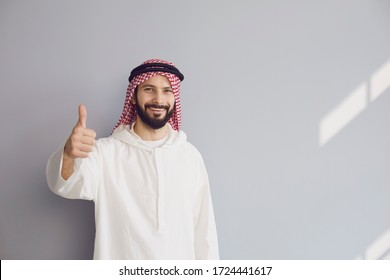 Attractive smiling arab man shows thumb up on gray background