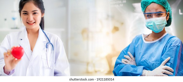 Attractive smiling Asian doctors wearing stethoscope and holding red heart shape in hand with blur patient crowd background in hospital, during coronavirus or covid-19 crisis, medical concept.