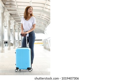 Attractive smiling asian girl in jeans holding Thai passport travel with blue luggage in the modern city. Beautiful traveler ready to go aboard walking to her destination on sunny day. With copyspace.