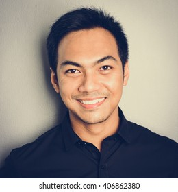 Attractive smiling Asian man on light gray background - vintage tone effect