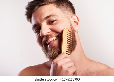 Attractive smiling Bearded man  holding a comp for beard standing above grey background