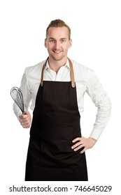 Attractive smiling blonde chef, standing against a white background wearing a white shirt and black apron with a big smile.
