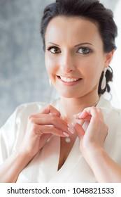 An attractive smiling brunette adjusting her silver pendant - a bride preparing for wedding