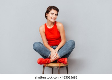 Attractive smiling brunette woman sitting on the chair over gray background