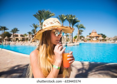 Attractive smiling brunette woman in summer with cocktail and straw hat