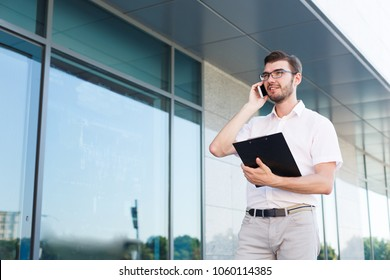 Attractive smiling businessman in eyeglasses is holding clipboard and talking on mobile phone while standing near modern office building, copy space. Business and communication concept