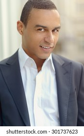 Attractive smiling businessman with his collar unbuttoned looking at the camera, closeup head and shoulders
