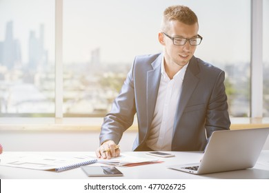 Attractive smiling businessman in suit and glasses working on project at table with electronic devices and paperwork