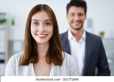 attractive smiling businesswoman standing inside the workplace with colleague in background