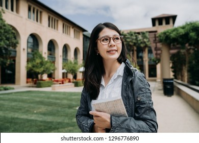 Attractive smiling charming asian young girl student with school book relaxing walking in university outdoor. college lady enjoy sunshine at the park in stanford surrounding by green grass and trees.
