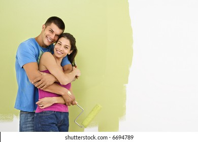 Attractive smiling couple posing in front of partially painted wall holding paint roller.