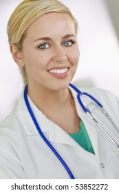 An attractive smiling female doctor wearing a white coat and stethoscope in a hospital.