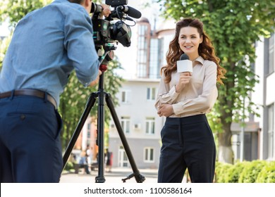 attractive smiling female journalist with microphone and cameraman