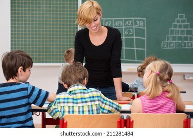 Attractive smiling female teacher in class talking to three young students, a small girl and two boys, seated together at a desk