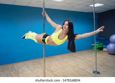 Attractive smiling girl on pylon hanging horizontally and holding with one hand at dance studio background. Athletic professional pole dancer demonstrating Angel element. Female stripper training