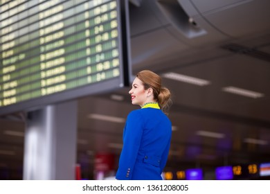 attractive smiling girl stewardess against the background of information display at the international airport. Elegant flight attendant on the background of ariivals - departures board