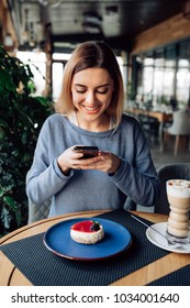 Attractive smiling girl taking photo of tasty cake, using smartphone, spending time at cafe with cup of latte. Dressed in sweater.