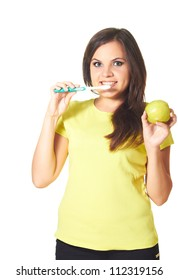 Attractive smiling girl in a yellow shirt holding in her right hand a toothbrush, and in the left hand holds an apple. Isolated on white background