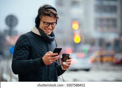 Attractive smiling guy listening to music in headphones, using his mobile phone, holds cup of coffee, standing on the street. Dressed in warm jacket.