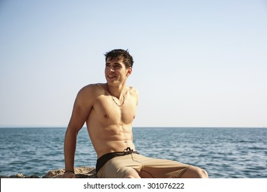 Attractive smiling handsome young man sitting on rock by sea or ocean shore with wet hair, looking in the distance, profile view