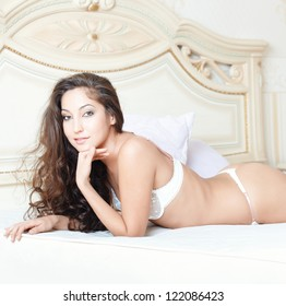 Attractive smiling lady laying on the bed