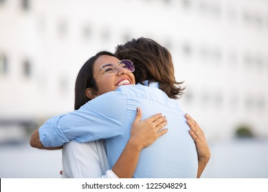 Attractive smiling Latin woman hugging man on urban street. Beautiful successful couple embracing in city. Togetherness concept