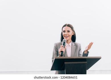 attractive smiling lecturer talking into microphone and gesturing at podium tribune during seminar in conference hall