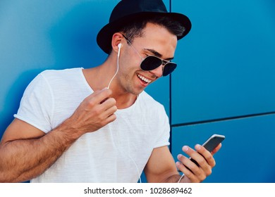Attractive smiling man in sunglasses looking at smartphone screen, watching a movie in earphones. Wearing stylish clothes. Standing near the wall, outdoors.