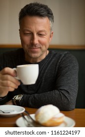 Attractive smiling mid adult man drinking morning coffee in cafe, image toned. Handsome single man in cafe