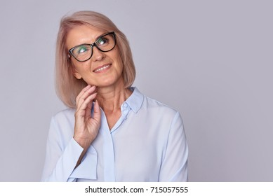attractive smiling old business woman wearing glasses. Isolated on grey. Studio shot