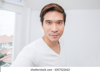Attractive smiling positive asian  man selfie with his smartphone. Closeup portrait of asian handsome guy with isolated on white background.