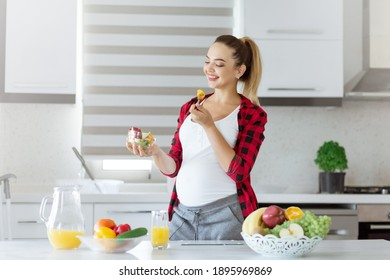 Attractive smiling pregnant woman holding a bowl of salad while standing in the kitchen,lifestyle at home