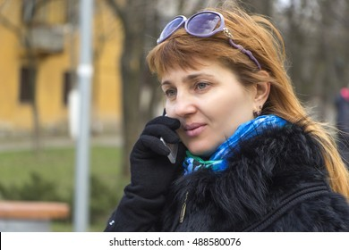 Attractive smiling red-haired girl talking by mobile phone outdoor. Green eyes, sunglasses on hair, black gloves on hands. Dressed in a fur vest.