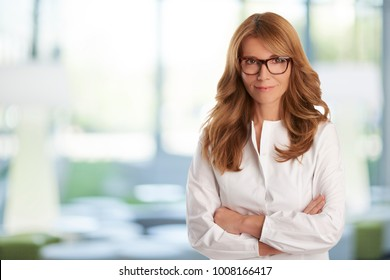 Attractive smiling sales woman wearing white shirt and standing at the office with arms crossed while ooking at camera.