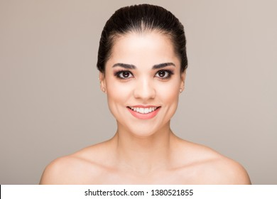 Attractive smiling woman with bare shoulders against beige background