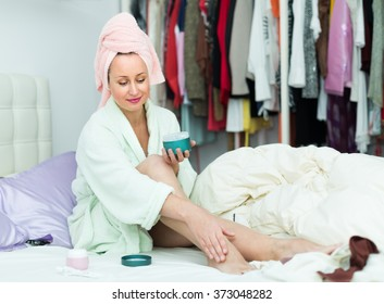 Attractive smiling woman in bathrobe sitting on bed and putting cream on legs